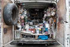 Interior of a home decorator`s van photographed from the rear, full of old tins of paint accessories, brushes and other supplies