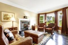 Interior home luxuoso com chaminé, as cadeiras antigas e o sofá de couro fotografia de stock