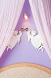 Interior of honeymoon room. Two angels with horns over bed Royalty Free Stock Photo