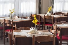 Interior of a hotel restaurant or dining room with yellow flowers.  royalty free stock image