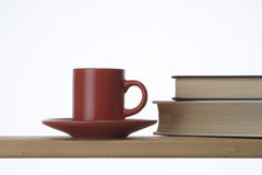 Interior image. Red coffee cup and saucer by some books on table Royalty Free Stock Image