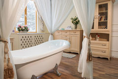 Interior images of bathroom in classic style. Bathroom in classic style. Interior shot of classic freestanding bathtub with curtains standing against elegant Stock Photography