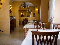 Interior of italian restaurant. Example of restaurant interior. Brown, wooden chair in the foreground. Tables covered with white tablecloth. Wine glass on the Stock Photo