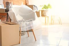 Interior items and packed carton boxes in room. Moving house concept royalty free stock image