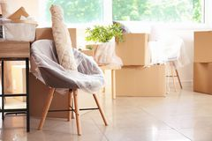 Interior items and packed carton boxes in room. Moving house concept royalty free stock images