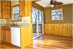 Interior kitchen, den, area of a rustic style home. Home interior showing kitchen area,den,and sliding glass doors leading to a back deck stock images