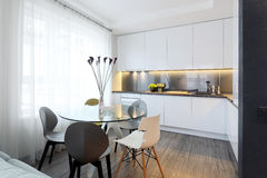 Interior - kitchen. Interior - white modern kitchen and a glass dining table with chairs Royalty Free Stock Photos