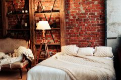 Interior with a large bed and a brick wall. 1 Royalty Free Stock Image