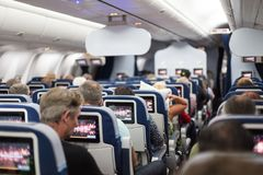 Interior of large commercial airplane with passengers on seats waiting to taik off. Royalty Free Stock Photography