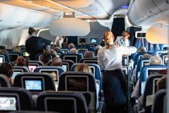 Interior of large commercial airplane with stewardesses serving passengers on seats during flight. Interior of large commercial airplane with flight attandants stock image