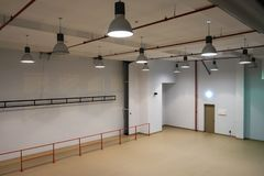 Interior of a large emty room. With lights on the celling stock photography