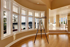 Interior of large living room with telescope by large six pane window. Royalty Free Stock Image