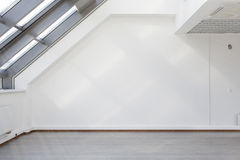 The interior with a large window in the ceiling. And patches of sunlight on the white wall stock photography
