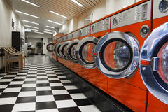Interior of laundromat. With orange washing machines royalty free stock photos
