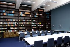 The interior of the library, blue and brown colors. Bookcases with books, white tables stock images