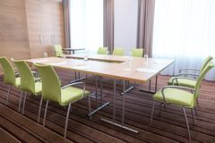 Interior of light committee room furnished with modern table and green chairs Royalty Free Stock Image