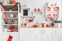 Interior light grey kitchen and red christmas decor. Preparing lunch at home on the kitchen concept. Interior light grey kitchen and red christmas decor stock photography