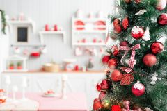 Interior light grey kitchen and red christmas decor. Preparing lunch at home on the kitchen concept. Focus on the branches of fir stock photography