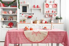 Interior light grey kitchen and red christmas decor. Preparing lunch at home on the kitchen concept. Focus on table and. Interior light grey kitchen and red royalty free stock photo