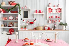 Interior light grey kitchen and red christmas decor. Preparing lunch at home on the kitchen concept. Interior light grey kitchen and red christmas decor royalty free stock photos