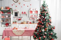 Interior light grey kitchen and red christmas decor. Preparing lunch at home on the kitchen concept. Interior light grey kitchen and red christmas decor stock photo