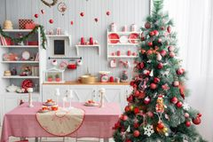Interior light grey kitchen and red christmas decor. Preparing lunch at home on the kitchen concept. Focus on tree. Interior light grey kitchen and red christmas Stock Photography