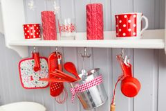 Shelves with dishes. Interior light grey kitchen and red christmas decor. Preparing lunch at home on the kitchen concept. Interior light grey kitchen and red royalty free stock image