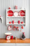 Shelves with dishes. Interior light grey kitchen and red christmas decor. Preparing lunch at home on the kitchen concept. Interior light grey kitchen and red stock image