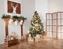 Interior living room with a Christmas tree and gifts.