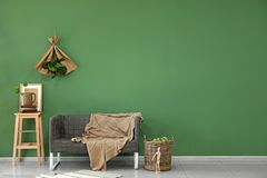 Interior of living room with comfortable sofa near color wall royalty free stock photography