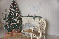 Interior of the living room with a fireplace, decorated for the New Year with a big Christmas tree and lots of presents Royalty Free Stock Images
