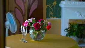 Interior living room, red roses in a vase on a table. Wine glasses for wine, fan cools room, white fireplace with green flowers stock video footage