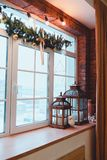 Loft interior. Window view. Christmas time. The interior of the loft. View of a window with red brick wall and Christmas decorations Stock Images
