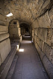 Interior of a long corridor an ancient stone structure in the a. Interior of a long corridor with a floor of large slabs of an ancient stone structure in the stock images