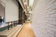 Interior of a long corridor with white brick wall.  Royalty Free Stock Photography