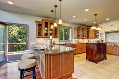 Interior luxuoso da sala da cozinha com armários e partes superiores contrárias do granito Fotografia de Stock Royalty Free