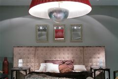 Interior with luxurious bed. Three mirrors in frame on luxurious bed with soft back stock photo