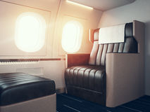 Interior of luxury airplane. Empty leather chair, sunlight illuminator. Horizontal mockup. 3d render. Photo of luxury airplane interior. Blank digital panel Stock Images