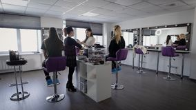 Interior of luxury beauty salon with two professional experts and two female models sitting. Professional visagistes are. Working with young girls and applying stock video footage