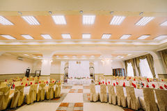 Interior of luxury wedding hall with rich decorated head table at background.  Royalty Free Stock Image