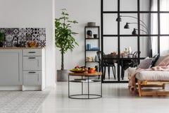 Interior mínimo blanco y negro de la cocina con la planta de pantano en pote y cosas en la mesa de centro fotos de archivo libres de regalías