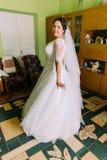 Interior magnífico en el vestido de boda blanco, concepto de la novia en casa de las preparaciones Retrato integral Imagen de archivo libre de regalías