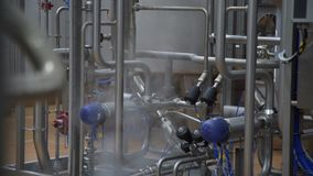 Stainless steel temperature control valves and pipes in modern dairy factory. Equipment at dairy plant. stock video