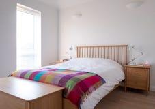 Interior minimalista do quarto com mobília de madeira do quarto, as paredes pintadas brancas, fundamento branco e a cobertura col fotografia de stock