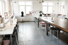 Empty Fashion Atelier Interior. Interior of modern atelier workshop with wooden workstation in foreground and sewing dummies, no people, copy space background Stock Photos