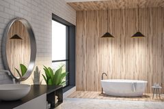 Brick and wooden bathroom interior, round tub. Interior of modern bathroom with white brick and wooden walls, a roundish bathtub and a sink. Loft window with stock illustration