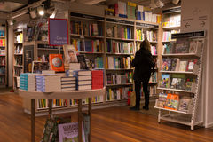 Interior of a modern bookshop with woman browsing the collection. Royalty Free Stock Photography