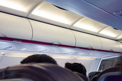 Interior of modern commercial airplane with passengers on their seats. Inside airplane Stock Photography