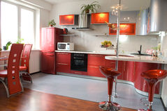 Interior of modern kitchen with a bar counter in red tones Royalty Free Stock Photography