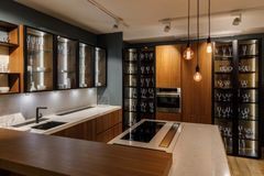 Interior of modern kitchen with glass cabinets and decorative bulbs stock image